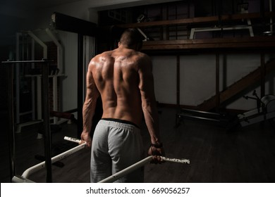 Model Doing Heavy Weight Exercise For Trapezius On Machine