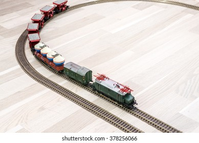 Model electric train on wooden floor, game for kids