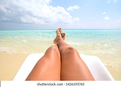 A model enjoys life on a sand bank in Maldive. Paradise on Earth with deserted beaches. Suntanning and relaxing under the tropical sun.