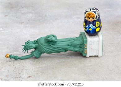 A model of a fallen Statue of Liberty with a small Russian Matryoshka doll standing on top of it (concept)