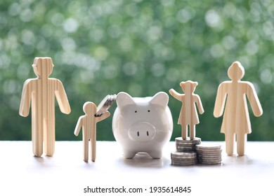 Model family and with piggy bank and stack of coins money on natural green background,Save money for prepare in future and family finance concept