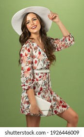 model in fashion with floral dress and white hat , looking up with a great smile . on green background