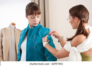Model fitting by professional female fashion designer studio