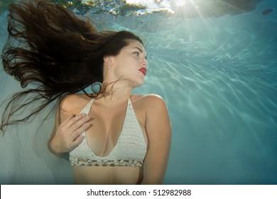 Model with flowing brunette hair underwater