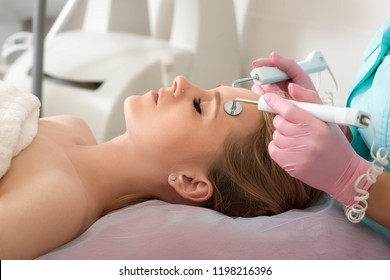 Model getting cleansing facial treatment therapy massage in a beauty SPA salon. Cleansing, exfoliation, rejuvenation and moisture procedures in cosmetology clinic. Model and Doctor.