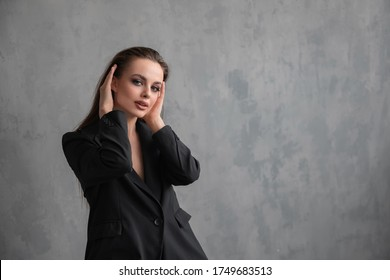 model girl in a black suit on a background of a gray wall