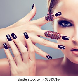 Model  girl  with burgundy manicure  nail and fashion jewelry   rings  . Beauty , fashion and cosmetics