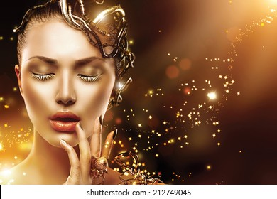 Model Girl face with gold skin, nails, make-up and accessories. Fashion Magic Woman with holiday golden makeup