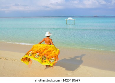 A model girl poses on a beautiful paradise beach in Maldive. Paradise on earth. Holiday on a sandbank.