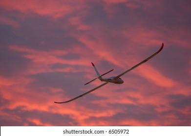Model glider plane flying at sunset