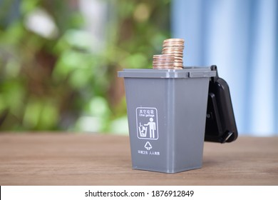 A model of a gray trash can containing recyclable trash in the garbage sorting process opens the lid and comes out with dollar coins