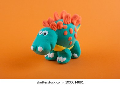 Model of green Stegosaurus on orange background