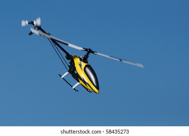 a model helicopter in flight, blue sky background