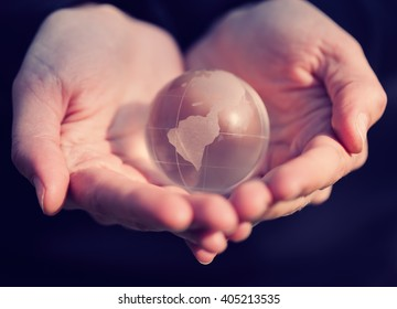 Model holding a glass globe in hands. Good concept for care, environment, conservation and unity.