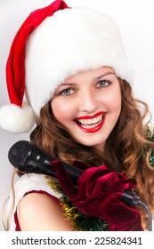 model holding karaoke and wearing christmas hat against white background