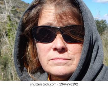 Model in hoodie and sunglasses.