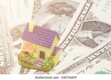 A model of a house in the background of money. Toned