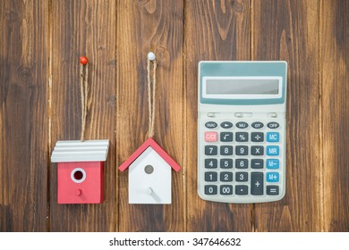 model house with Calculator on wooden background
