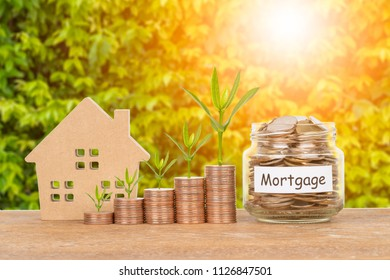 Model house, coin stack, and money jar on white background mortgage saving concept