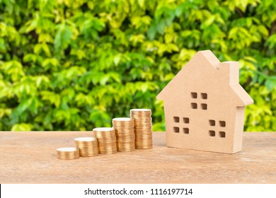 Model house and coin stack on green tree background mortgage saving concept