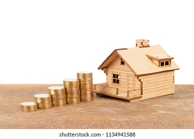 Model house and coin stack on white background mortgage saving concept