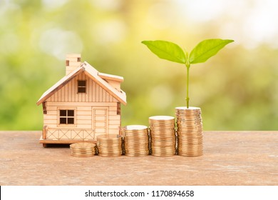 Model house and coin stack with plant on green tree background mortgage saving concept