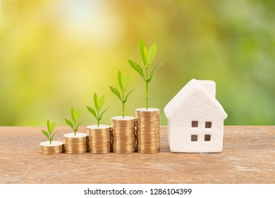 Model house and coin stack with tree on blur green background mortgage saving concept