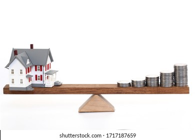 Model house and coins balancing on seesaw against white background