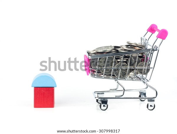 Model of house with coins on shopping cart or trolley - Financial concept