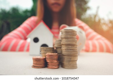 Model of house with coins on wooden table on blurred background, concept saving money for house and future.