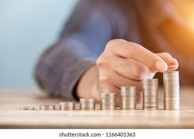 Model of house with coins on wooden table