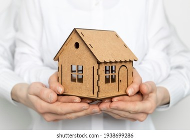 The model house is in the hands of a family, a man and a woman. Concept for mortgage loan or real estate purchase.