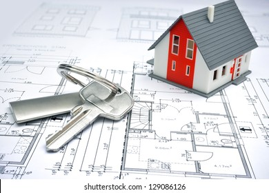 model of a house and key ring on a blueprint
