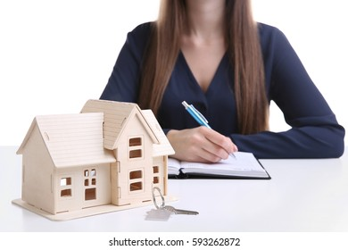 Model of house with key and woman on background
