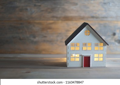 Model house with lights on inside over wood with space
