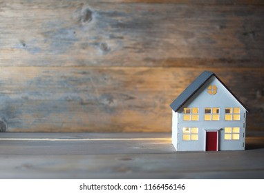 Model house with lights on inside over a wooden background