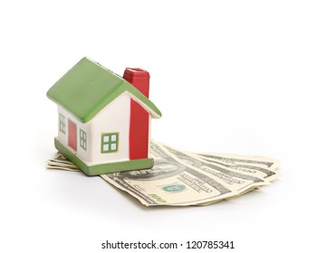 Model of a house lying on some banknotes isolated on white background