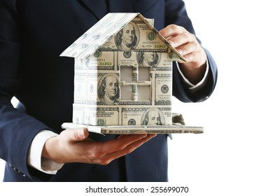 Model of house made of money in male hands isolated on white background