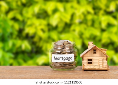 Model house and money coin jar on white background mortgage saving concept