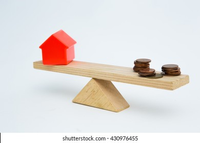 Model house and money coins balancing on a seesaw. Concept selling a house for the money