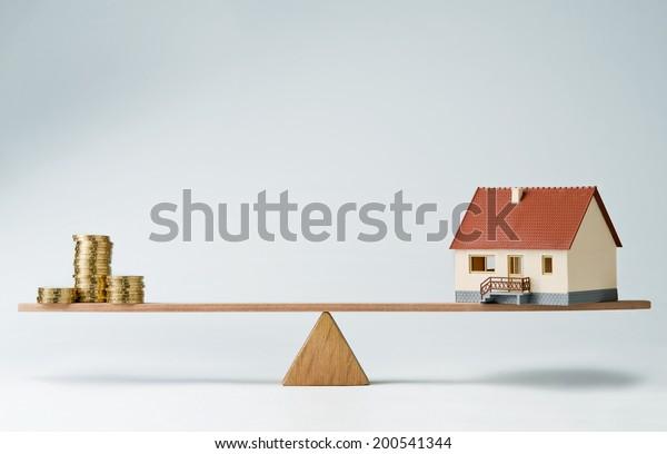 Monedas de la casa modelo y monedas de dinero equilibradas en un vaso de agua