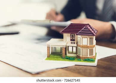 Model house on a desk with floor plans for a project and a real estate agent signing documents in blurred background