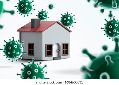 Model house on a white background with viruses around. It gives the message stay at home and work at home.