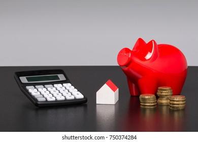 Model house, piggy bank with pocket calculator on a blueprint