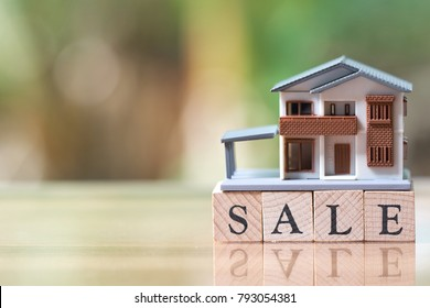 A model house model is placed on wood word sale . as background property real estate concept with copy space for your text or  design.