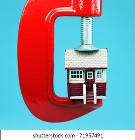 A model house in a red clam with alight blue background, indicating the pressure is on to meet the mortgage payments.