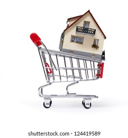 Model of the house in shopping cart on white background