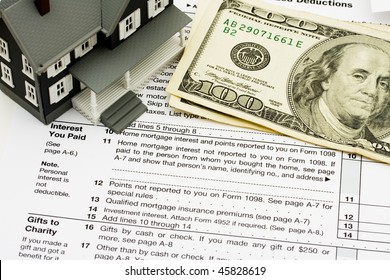 A model house sitting on tax papers, Deduct mortgage interest on taxes