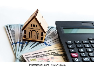The model of the house stands on the money. Planning savings money to buy a home, mortgage and real estate investment, saving for a buy house.
