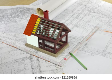 model of house wit plans and drafts on architect's desk